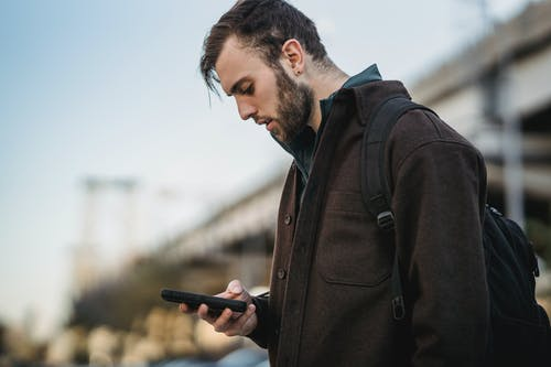 Side view of crop young unshaven male watching cellphone under light sky in town