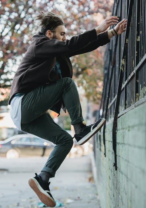 Side view of young agile male athlete in casual apparel ascending fence from city pathway during workout