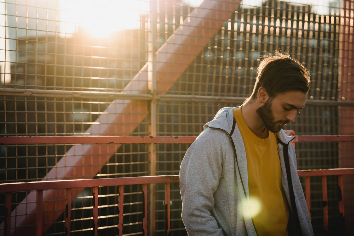 Young upset unshaven male in casual apparel looking down near grid fence in back lit in town