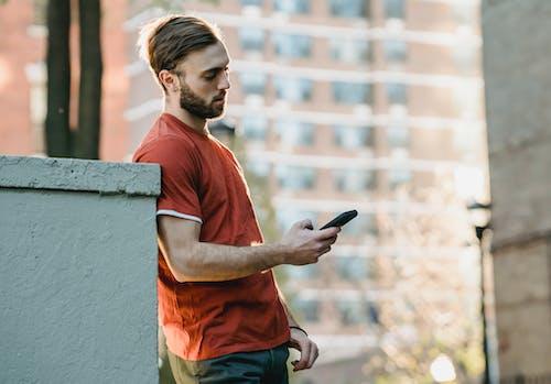 Focused bearded man watching smartphone in town
