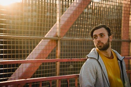 Dreamy unshaven man near grid fence in sunshine