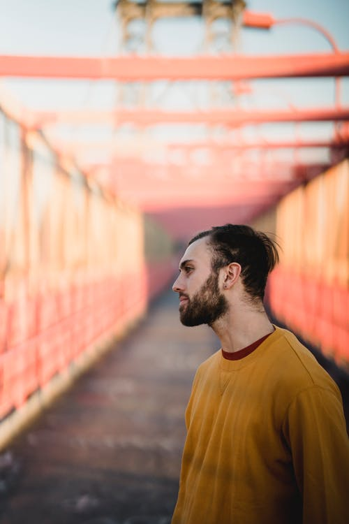 Side view of millennial hipster male in soft outfit looking away on bridge in town