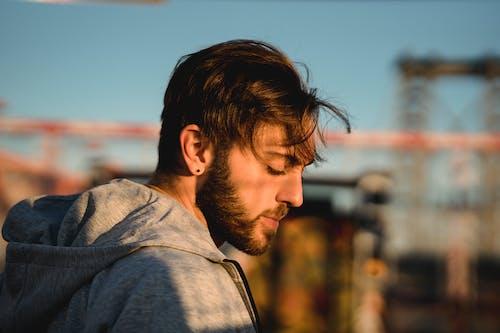Masculine man in hoodie in town in sunshine