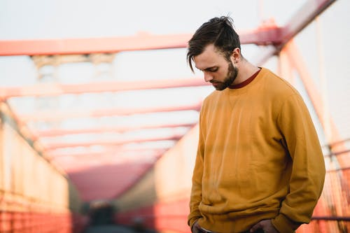 Young thoughtful bearded male in casual apparel with modern haircut looking down while standing with hands on hips in town