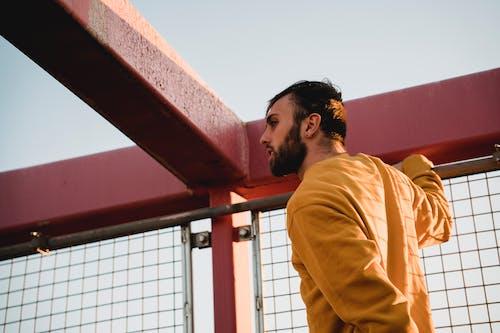 Hipster man near grid fence on bridge