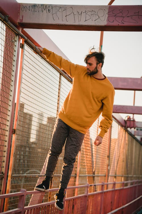 Young unshaven male in casual outfit standing on fence of city bridge while looking down on sunny day