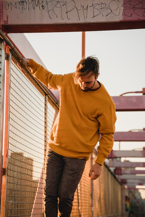 Young unshaven male with raised arm near grid fence of urban bridge looking down in back lit
