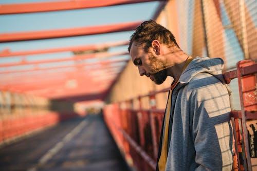 Side view of unshaven millennial guy in hoodie looking down on road of city bridge in sunlight