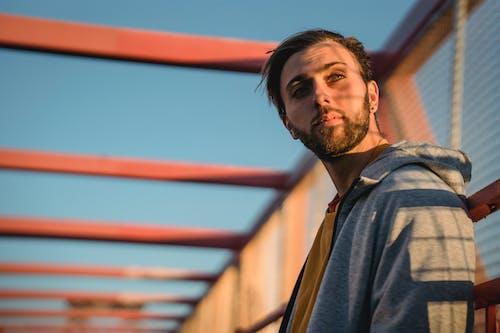 Contemplative millennial man on urban bridge in soft sunlight