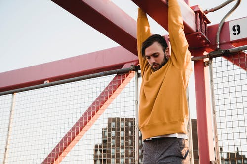 Strong man hanging on metal construction