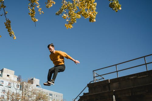 Active man jumping from high structure