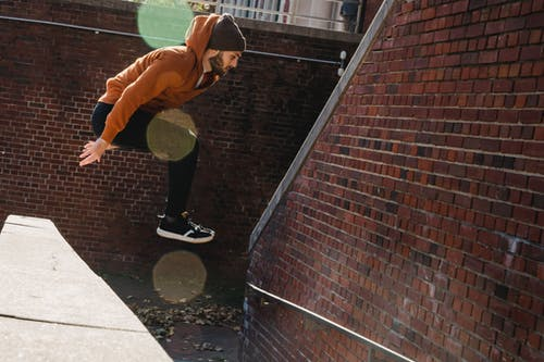 Full body side view of fearless bearded male jumping off concrete border near brick walls on street during sportive training