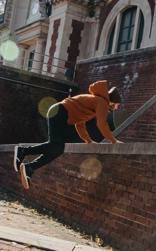 Energetic man jumping over barrier