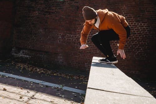 Full body side view of sportive male in hat jumping on concrete border against brick wall during parkour training on street
