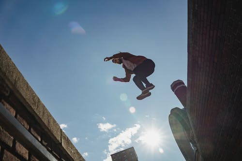 Active man jumping from brick wall