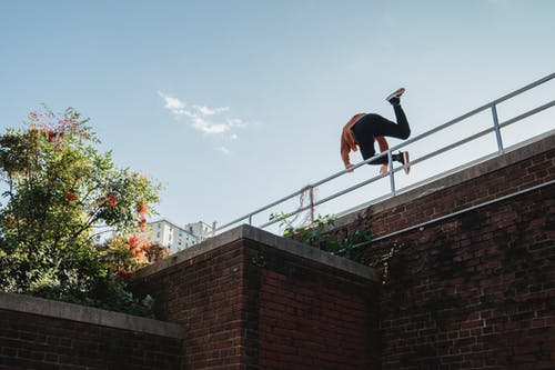 From below back view of anonymous sportive male jumping over metal banister of brick wall during parkour training on street