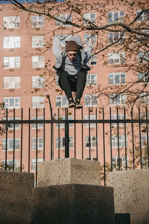 Sporty man jumping on concrete pillar