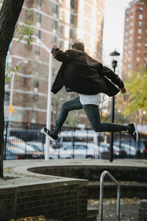 Full body back view of sportive male jumping above ground in street during parkour exercise against blurred buildings in city