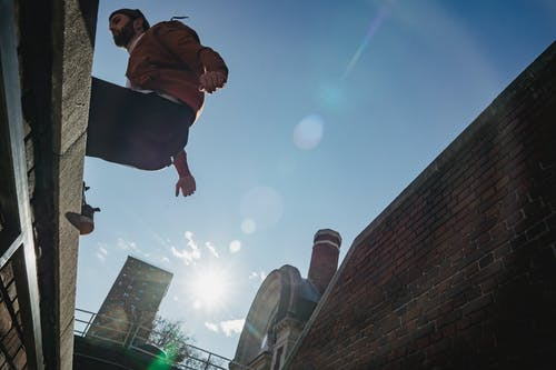 From below of sportive fearless bearded male jumping on roof against blue sky in sunlight on street during parkour training