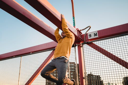 Hipster man hanging on beam of urban bridge during training