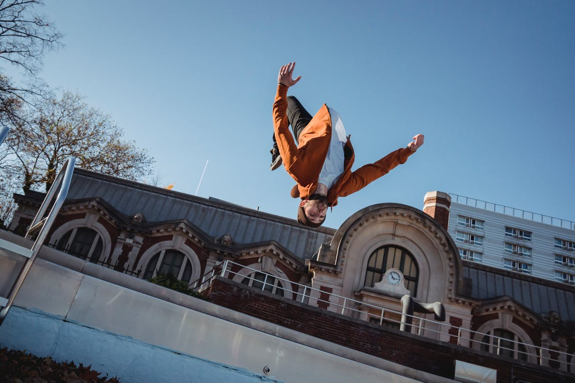 From below of sportsman jumping in air while demonstrating upside down trick during training against urban building