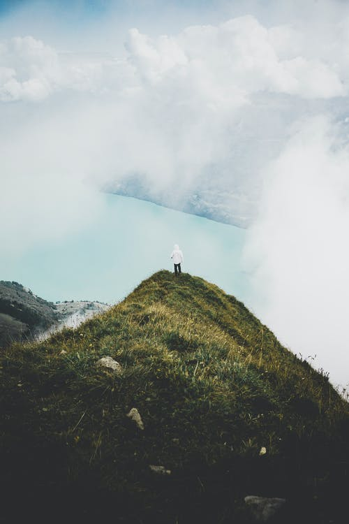 Person Standing on Green Grass Mountain