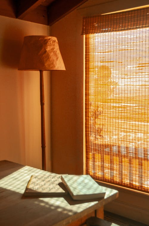 Room interior with textbooks on table against floor lamp and wicker curtain in house on sunny day