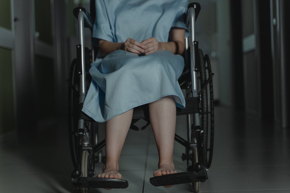 A woman in blue robe sitting on black wheelchair.  Photo: Pexels