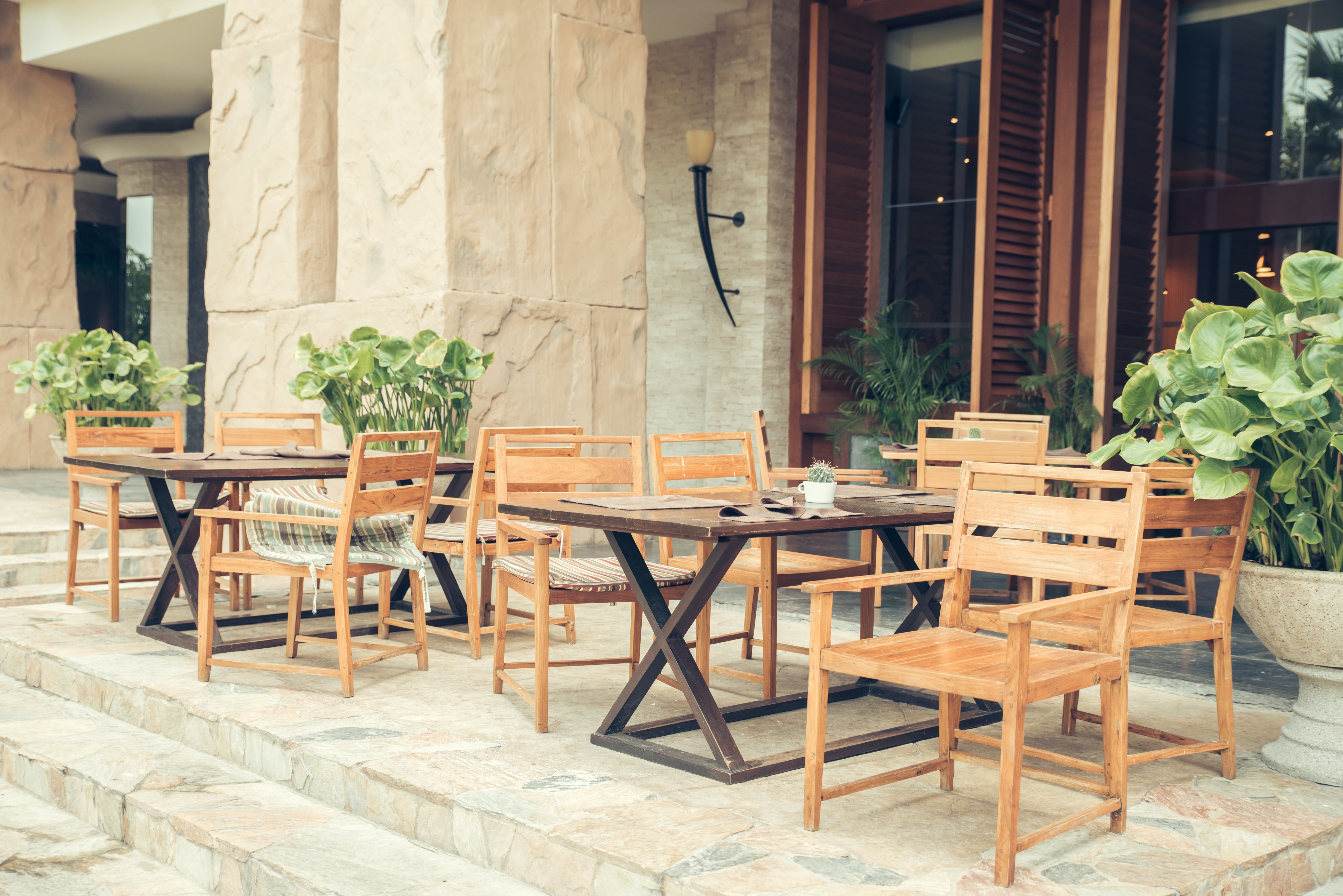 Two Sets of Brown Wooden Table and Chairs Outside Store