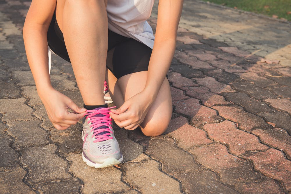 Frau bindet sich den Schuh zu - Quelle: Pexels