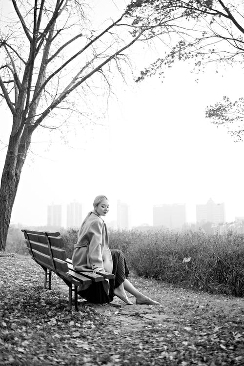 Happy woman smiling and resting on bench in foggy park