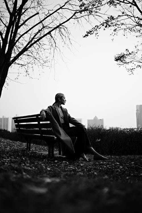 Black and white of cheerful female smiling and resting on bench of park