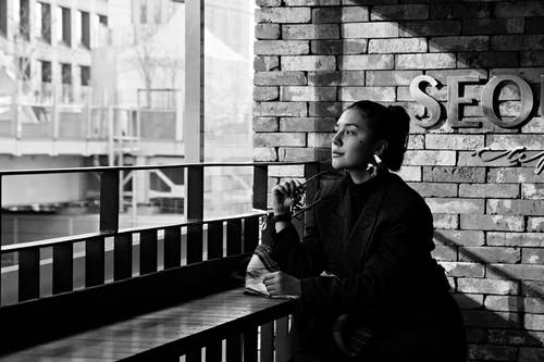 Black and white of thoughtful young female resting at table in coffee shop and looking away