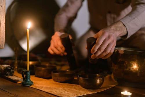 Person Holding Lighted Candles on Brown Wooden Table
