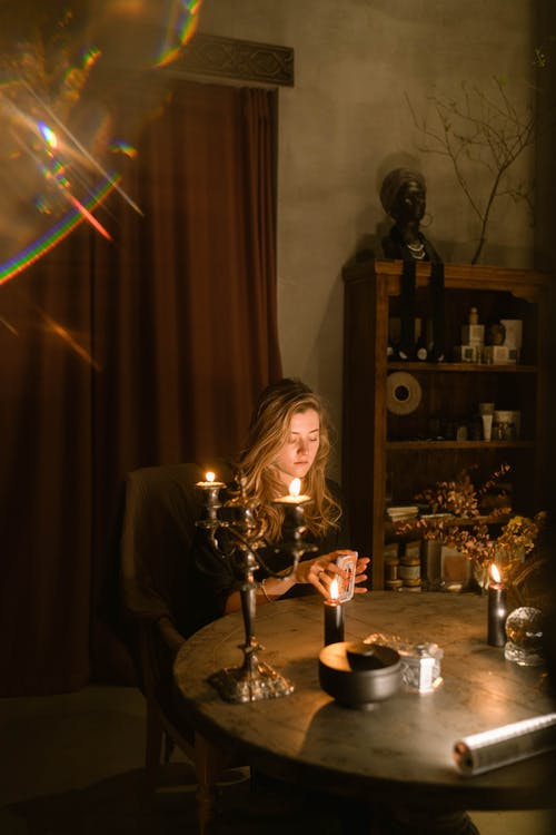 Smiling Woman in Black Long Sleeve Shirt Sitting Beside Table With Lighted Candles