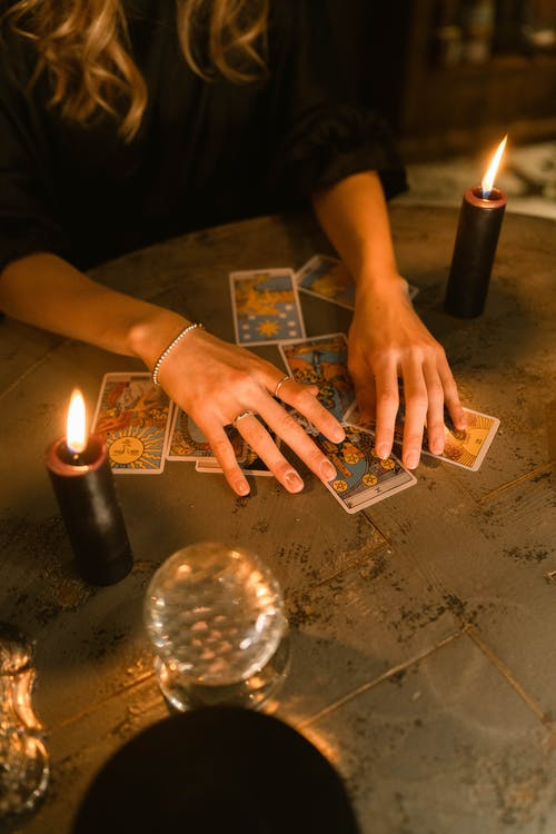 Person Holding Lighter and Playing Cards