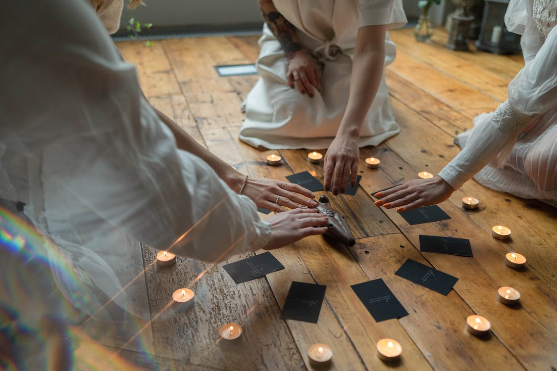 Person in White Robe Holding Brown Wooden Board Game