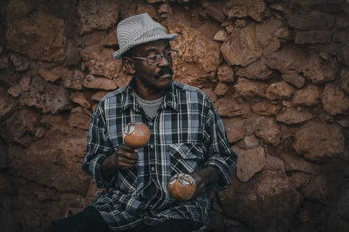 Thoughtful Indian man with decorative balls near stone wall