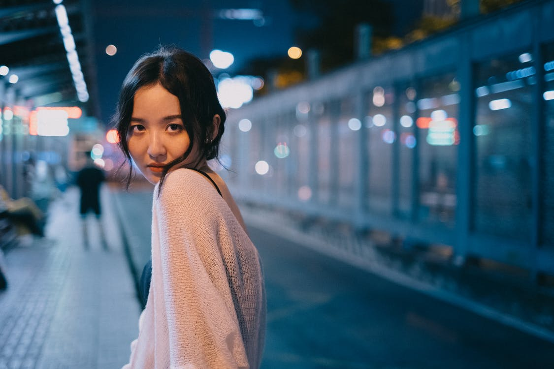 Content slim ethnic female looking over shoulder on blurred background of street with bright lights