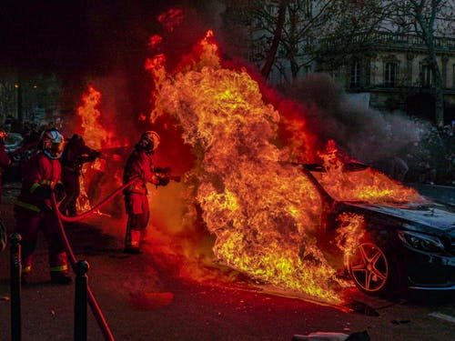 Firefighters Extinguishing a Burning Car