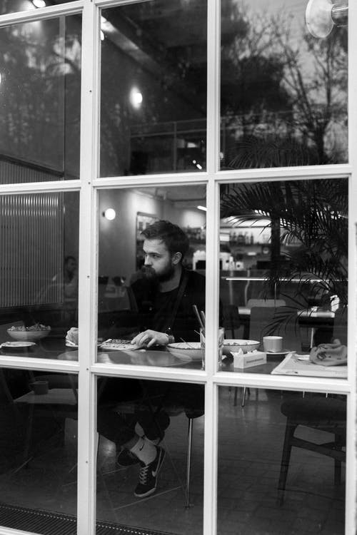 Stylish young man with beard having meal in cafe