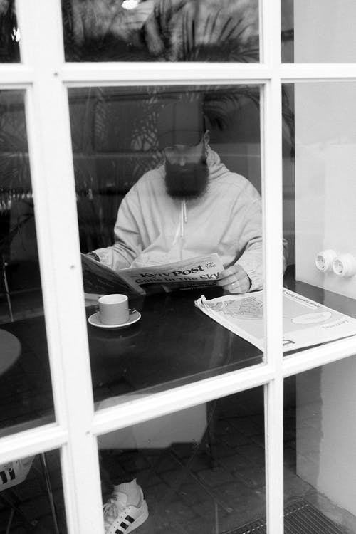 Black and white of pensive male with beard reading newspaper while resting at table in cafe