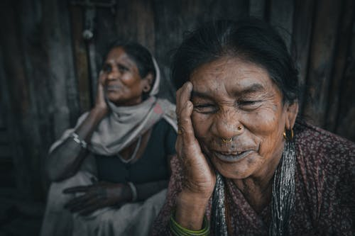 Cheerful senior Indian female friends touching faces in daytime