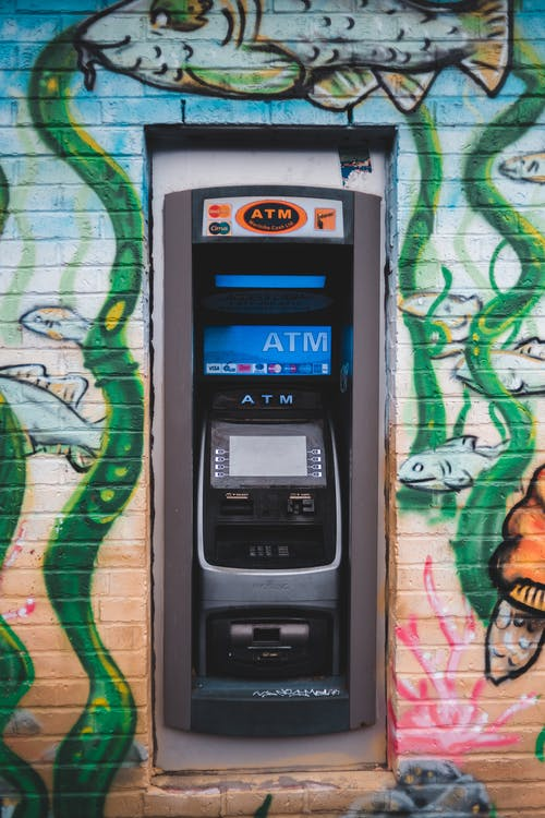 Modern ATM equipment on wall of urban building with bright contemporary street art