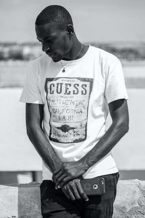 Black and white of wistful African American male in stylish t shirt and with cellphone looking down