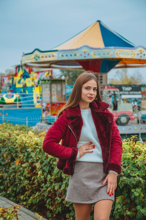 Attractive brown haired female in casual clothes standing against carousel and holding hand on waist while looking at camera