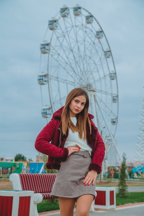 Low angle of female in trendy outfit holding hand on waist while standing in amusement park and looking at camera