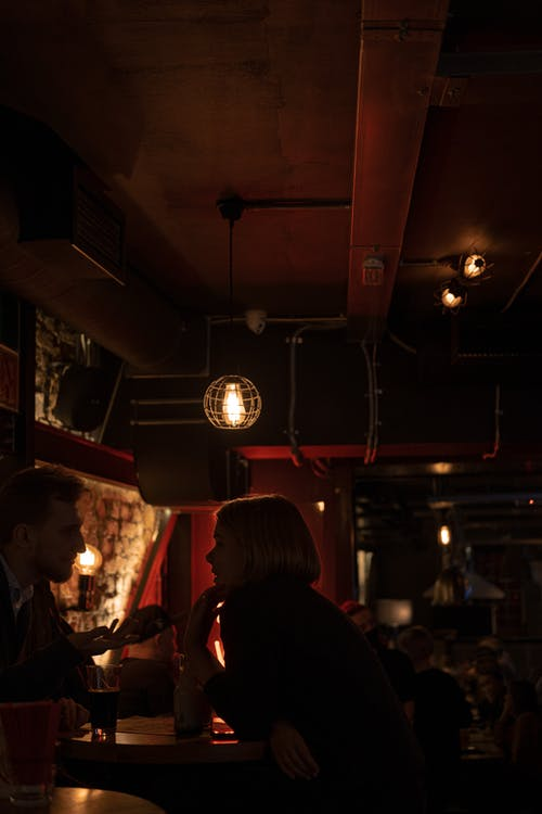 Side view of couple chatting while resting in dark building of old pub with bright lamps