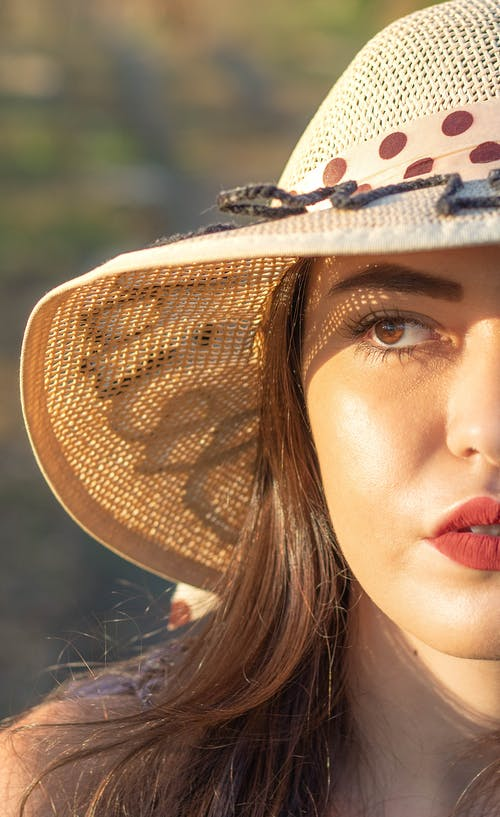 Woman with makeup and in summer hat in nature
