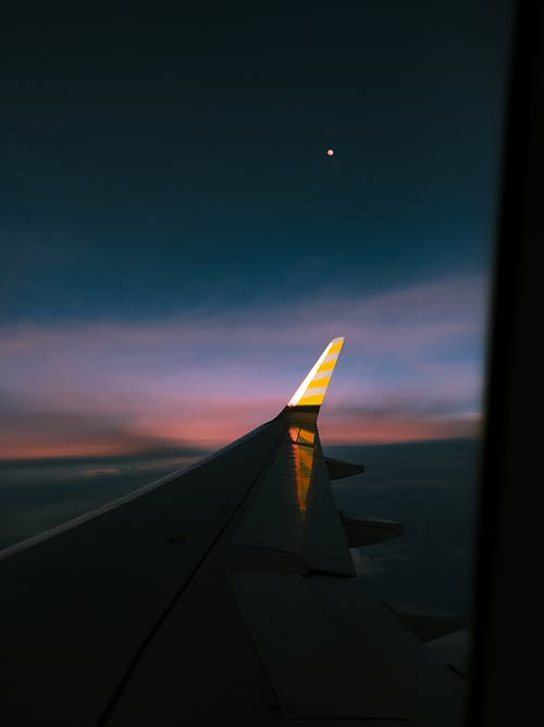 Through window of wing of modern aircraft flying over fluffy clouds in dark colorful sunset sky